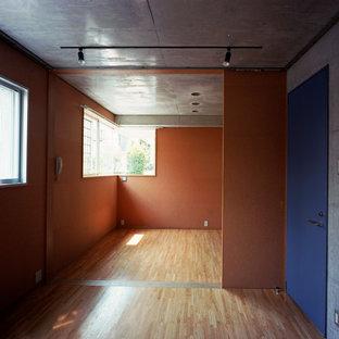 Imagen de dormitorio principal, minimalista, de tamaño medio, sin chimenea, con paredes blancas, suelo de madera en tonos medios, marco de chimenea de yeso y suelo marrón