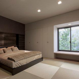 Ejemplo de dormitorio principal, actual, sin chimenea, con paredes beige, tatami y suelo verde