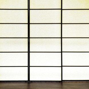 Foto di una camera matrimoniale con pareti bianche, pavimento in compensato e pavimento marrone