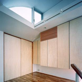 Réalisation d'une petite chambre parentale asiatique avec un mur blanc, un sol en bois brun, aucune cheminée, un manteau de cheminée en plâtre et un sol marron.
