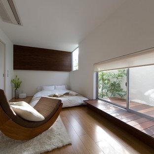 Idée de décoration pour une chambre asiatique avec un mur blanc, un sol en bois brun et aucune cheminée.