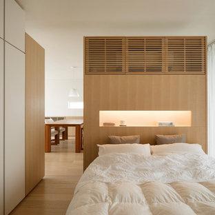 Idée de décoration pour une chambre parentale asiatique avec un mur blanc, un sol en bois clair et un sol beige.