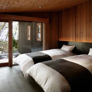 Immagine di una camera degli ospiti stile rurale con pareti marroni, parquet scuro e pavimento nero