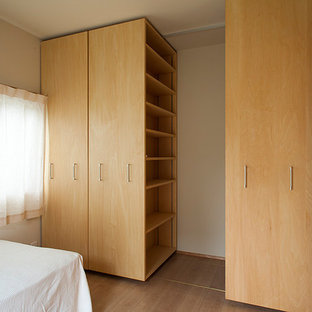 Idee per una camera matrimoniale country di medie dimensioni con pareti bianche, pavimento in compensato, camino sospeso e pavimento beige