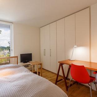 他の地域の小さいモダンスタイルのおしゃれな寝室 (白い壁、無垢フローリング、茶色い床)