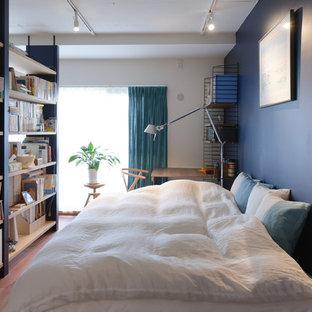 他の地域のコンテンポラリースタイルのおしゃれな寝室 (青い壁、無垢フローリング、茶色い床)