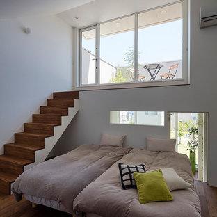 他の地域のモダンスタイルのおしゃれな主寝室 (白い壁、濃色無垢フローリング、暖炉なし、茶色い床) のレイアウト