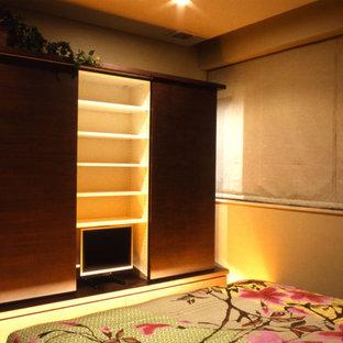 Foto di una camera matrimoniale etnica con pavimento in compensato, pavimento marrone e pareti beige