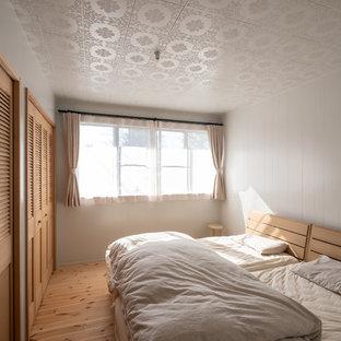 他の地域のカントリー風おしゃれな寝室 (白い壁、無垢フローリング、茶色い床)