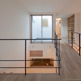 Inspiration för ett mellanstort funkis sovloft, med vita väggar, brunt golv och plywoodgolv