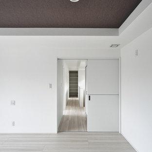 Foto di una camera matrimoniale minimalista con pareti bianche, pavimento in compensato e pavimento bianco