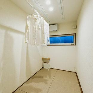 Inredning av ett modernt mellanstort gästrum, med tatamigolv, vita väggar och brunt golv