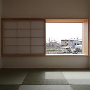 Modelo de habitación de invitados actual, pequeña, con paredes blancas, tatami y suelo verde