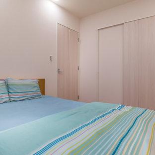 Esempio di una camera matrimoniale scandinava di medie dimensioni con pareti bianche, pavimento in compensato, nessun camino e pavimento marrone