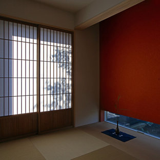 Example of a mid-sized guest tatami floor and brown floor bedroom design in Tokyo with red walls and no fireplace