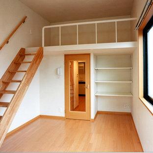 Modelo de dormitorio tipo loft, minimalista, de tamaño medio, con paredes blancas, suelo de contrachapado y suelo beige