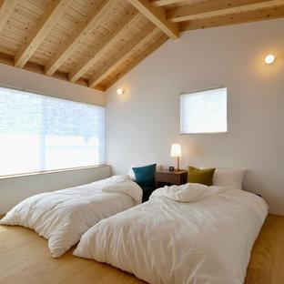 Exemple d'une chambre d'amis scandinave de taille moyenne avec un mur blanc et un sol en bois clair.