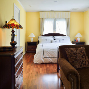 Design ideas for a mid-sized traditional master bedroom in Tokyo Suburbs with yellow walls, dark hardwood floors and brown floor.