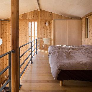 他の地域の中サイズのアジアンスタイルのおしゃれな主寝室 (茶色い壁、無垢フローリング、暖炉なし、茶色い床) のレイアウト