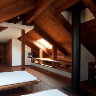 Стильный дизайн: спальня в восточном стиле с белыми стенами, темным паркетным полом, печью-буржуйкой и коричневым полом - последний тренд
