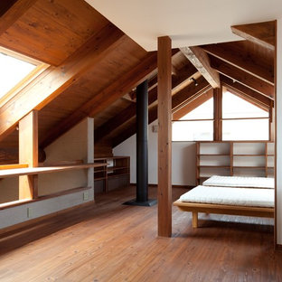 На фото: спальня в восточном стиле с белыми стенами, темным паркетным полом, печью-буржуйкой и коричневым полом с