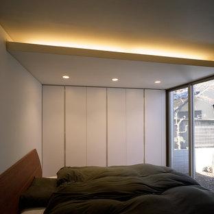 Ejemplo de dormitorio minimalista, pequeño, sin chimenea, con paredes blancas, suelo de madera clara, marco de chimenea de yeso y suelo beige