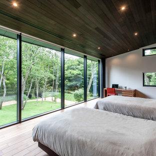 モダンスタイルのおしゃれな主寝室 (マルチカラーの壁、暖炉なし、茶色い床) のインテリア
