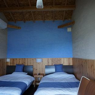 Diseño de habitación de invitados asiática con paredes azules, suelo de contrachapado y chimenea tradicional