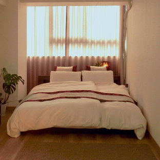 Imagen de dormitorio principal, asiático, de tamaño medio, con paredes blancas, suelo vinílico y suelo marrón