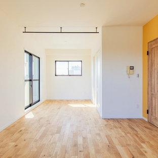 Foto de dormitorio principal, urbano, grande, sin chimenea, con paredes amarillas y suelo de madera clara