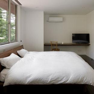 Immagine di una camera matrimoniale moderna con pareti bianche, pavimento marrone e pavimento in compensato