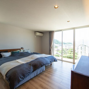 他の地域の大きいモダンスタイルのおしゃれな主寝室 (白い壁、無垢フローリング、茶色い床) のレイアウト