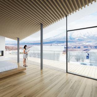 Diseño de dormitorio principal, contemporáneo, grande, con paredes blancas, suelo de madera en tonos medios, chimenea de doble cara, marco de chimenea de yeso y suelo beige