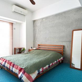他の地域のインダストリアルスタイルのおしゃれな主寝室 (グレーの壁、カーペット敷き、青い床) のインテリア