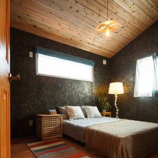 Immagine di una camera da letto etnica con pareti nere, pavimento in legno massello medio e pavimento marrone