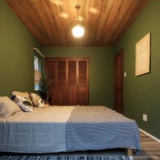 Ejemplo de dormitorio urbano con paredes verdes, suelo de madera en tonos medios y suelo marrón