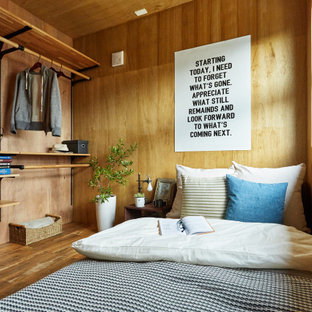 Design ideas for an industrial bedroom in Other with brown walls, medium hardwood floors, brown floor, wood and wood walls.