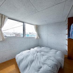 他の地域のコンテンポラリースタイルのおしゃれな寝室 (グレーの壁、無垢フローリング、茶色い床) のレイアウト