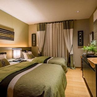Exemple d'une petit chambre parentale moderne avec un mur vert, un sol en contreplaqué et un sol marron.