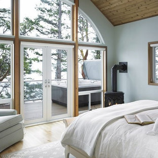 Example of a mountain style master light wood floor bedroom design in Tokyo Suburbs with white walls and a wood stove