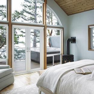 Ispirazione per una camera matrimoniale stile rurale con pareti bianche, parquet chiaro e stufa a legna