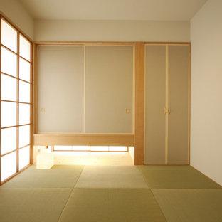 Cette image montre une petit chambre d'amis asiatique avec un mur beige et un sol de tatami.