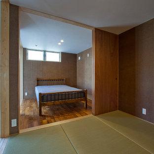 Esempio di una camera da letto etnica con pareti verdi, pavimento in compensato e pavimento marrone