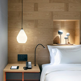 Immagine di un'ampia camera degli ospiti nordica con pareti marroni, parquet chiaro, nessun camino, pavimento marrone, soffitto in carta da parati e pareti in legno
