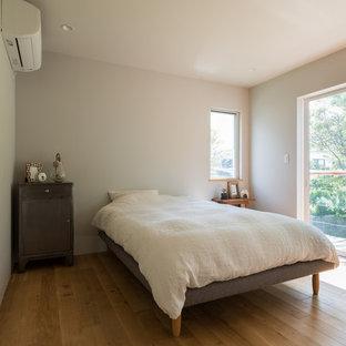 東京都下のコンテンポラリースタイルのおしゃれな主寝室 (グレーの壁、無垢フローリング、茶色い床) のインテリア