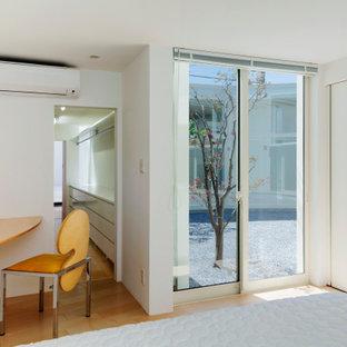 Immagine di una camera degli ospiti moderna con pareti bianche, pavimento in legno verniciato, nessun camino, pavimento beige, travi a vista e pareti in perlinato