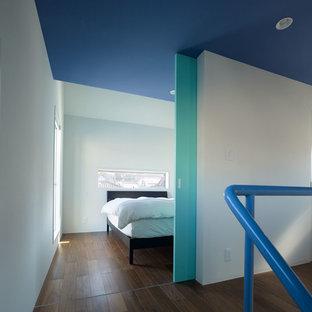 Esempio di una camera matrimoniale minimalista di medie dimensioni con pareti verdi, pavimento in compensato, nessun camino e pavimento marrone