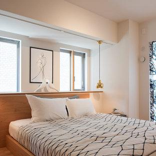 他の地域のアジアンスタイルの寝室の画像 (白い壁、無垢フローリング、茶色い床)