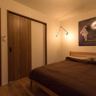Esempio di una camera matrimoniale stile rurale con pareti bianche, pavimento in compensato, nessun camino e pavimento marrone