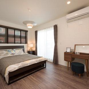 他の地域の中くらいのカントリー風おしゃれな主寝室 (グレーの壁、暖炉なし、茶色い床) のインテリア